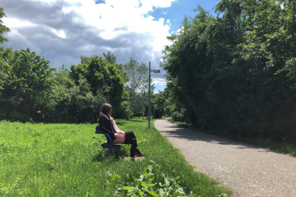 Frau sitzt auf einer Bank im Grünen
