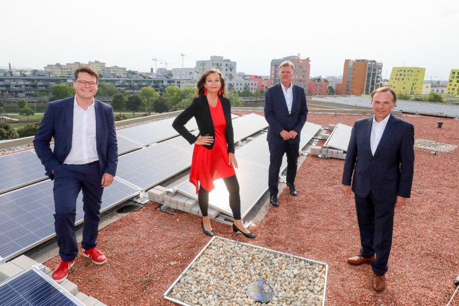 Personen vor auf einem Dach vor Solarpaneelen