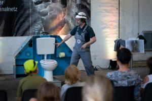 Karli Kanalarbeiter zeigt auf eine Toilette