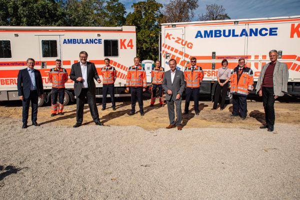 Gruppe von Personen mit Stadtrat Hacker und Bezirksvorsteher Gerald Bischof vor K-Zug Wägen der Wiener Rettung