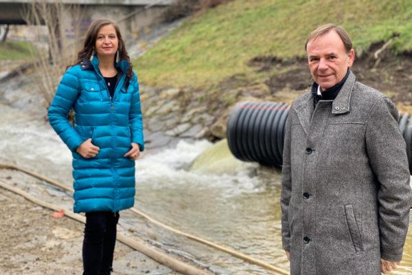 Ulli Sima und Gerald Bischof stehen auf der Baustelle der Liesingbachrenaturierung direkt neben dem Bach. Im Hintergrund sieht man den umgeleiteten Bach aus einem großen schwarzen Rohr in den hart verbauten Liesingbach reinfließen