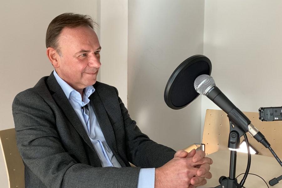 Bezirksvorsteher Gerald Bischof sitzend vor einem Microphon