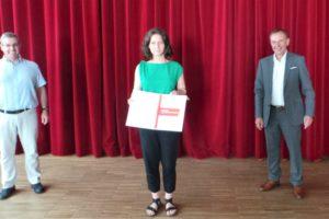 3 Personen stehen vor einem roten Vorhang, darunter Bezirksvorsteher Gerald Bischof