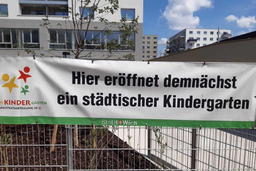 Transparent hängt auf einem Zaun mit dem Text Hier eröffnet demnächst ein städtischer Kindergarten