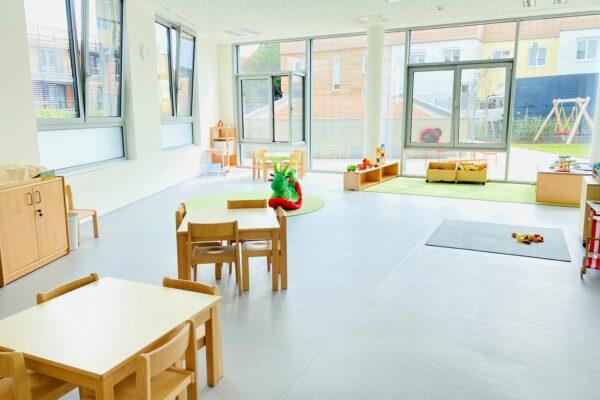 Kindergartengruppenraum Blickrichtung Fenster, im Vordergrund 2 Tische mit Sesseln rundherum