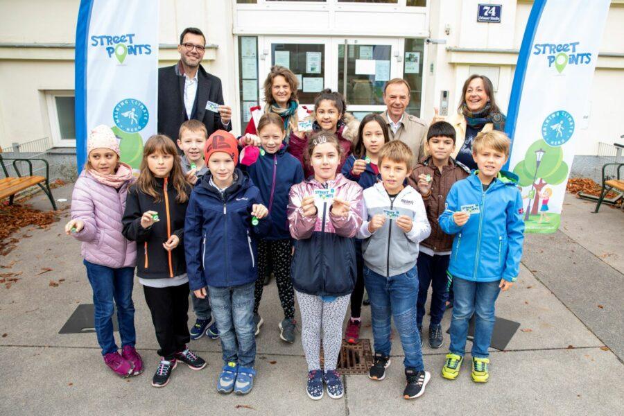 Gruppe von Kindern mit 4 Erwachsenen vor dem Eingang einer Volksschule